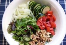 Assemble the mixed greens, fennel, zucchini, Ontario field tomato and walnuts for the August Harvest Vegetable Salad