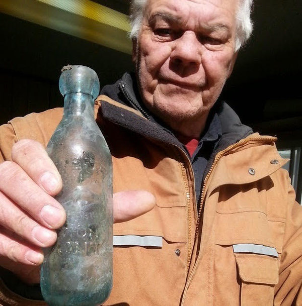 Saul Berringer holds an Alex Burns soda bottle from the 1890s that was recovered at the Forward Condos site in Toronto, photo courtesy of Dumpdiggers blog