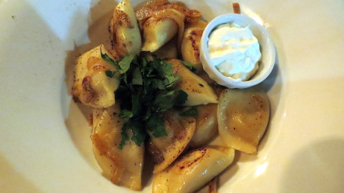 Perogies with mushroom and sauerkraut with sour cream at Schnitzel Hub Toronto