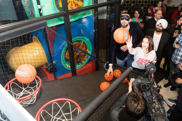 Guests shoot hoops with Toronto Raptors' Jonas Valanciunas at Paramount Fine Foods grand opening, photo credit Nick Merzetti