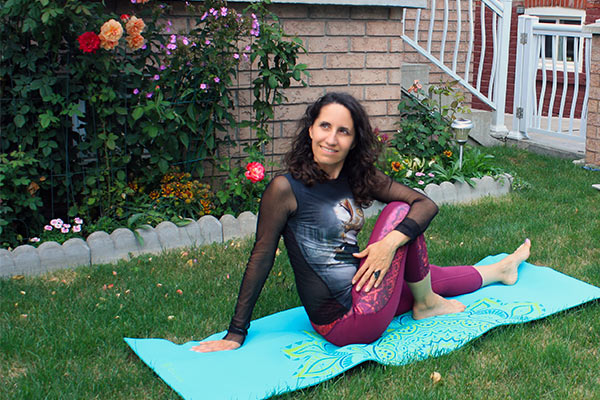 Taking the Gaiam premium yoga mat outdoors on the grass for seated twist.