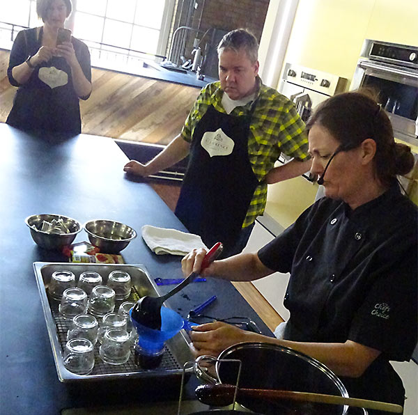 Using a funnel and ladle to fill the jar with grape jelly at Market Kitchen cooking classes.