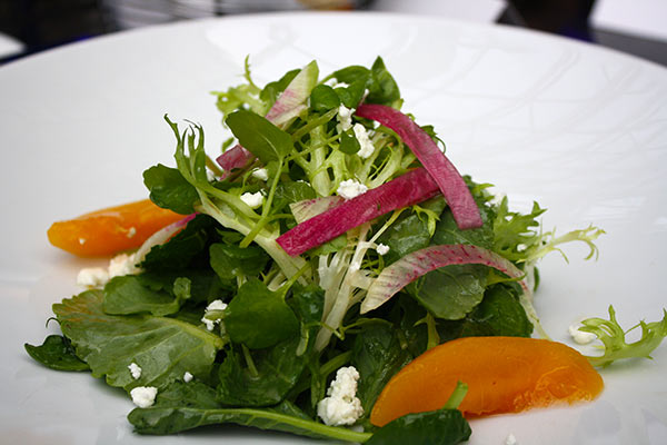 Leaves of Watercress & Baby Kale with compressed peaches, radish, goat cheese and citrus & honey basil vinaigrette on Summerlicious menu at Azure Restaurant