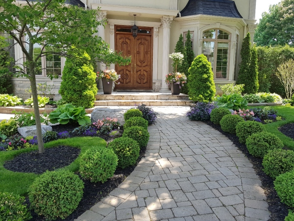 If you want to know how to create curb appeal for your home. create symmetry by planting shrubs on both sides of a walkway or porch.