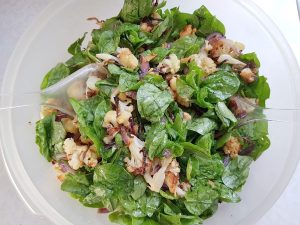Combine roasted cauliflower, red onion and mixed greens in a bowl.